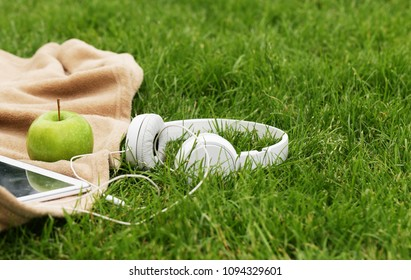 Headphones, electronic tablet and green apple for picnic in park on green grass