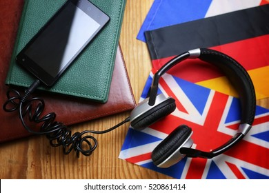 headphones and flag on a wooden background concept course language