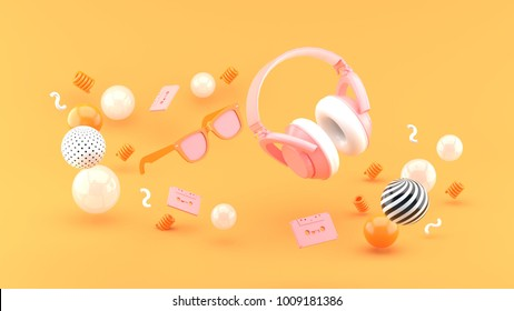 Headphones and glasses float between the balls on the orange background 3d render
