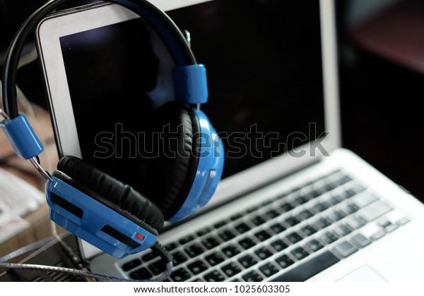 Headphones Hang On Notebook Computer Laptop Stock Photo