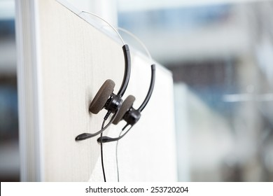 Headphones hanging on cubicle partition in empty office