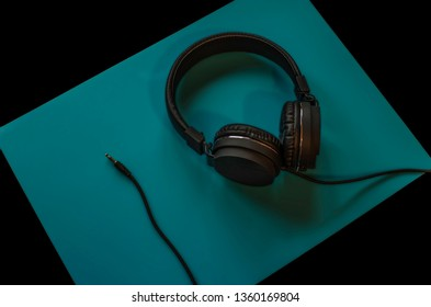 Headphones isolated on black and blue background. Technology.