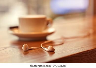Headphones lying near cup of coffee