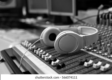 Headphones lying on the mixing console in black and white