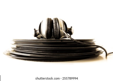 Headphones lying on a stack of vinyl records. Music concept.