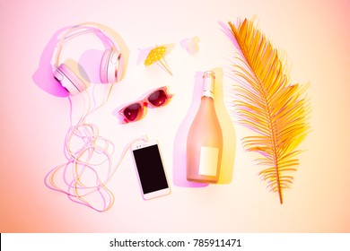 Headphones, mobile phone (smartphone), champagne bottle, sunglasses and exotic leaf. Summer fun vibes, holiday leisure or party concept. Pastel pink background, from above (top view, flat lay).