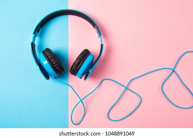Headphones on blue and pink background, top view