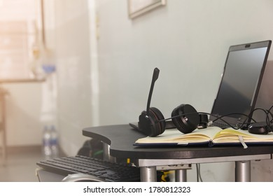Headphones are on the desk in the house with laptop and working accessory place nearby