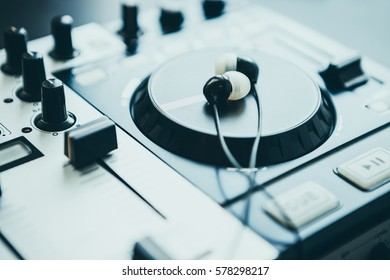Headphones on DJ midi controller turntable. Close up on sound equipment. Knobs, fader, jog wheel