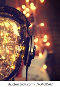 Headphones on a glass head with Christmas lights, Christmas music, Rock guitar with lights in the background