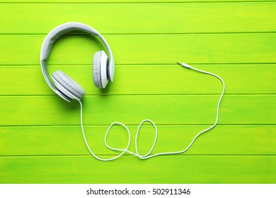 Headphones on a green wooden table, close up