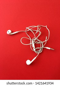 Headphones on a red background the wires of the headphones are tangled. White smartphone earphones with tangled cord