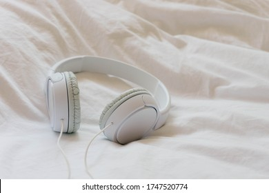Headphones over a bed. Relaxing moment concept. After-work disconnection. Headphones detail.
