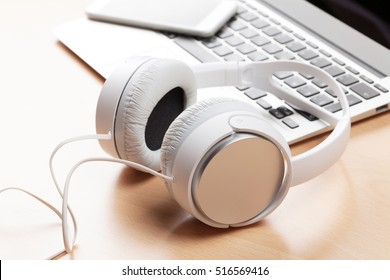 Headphones over laptop on wooden desk table. Music concept