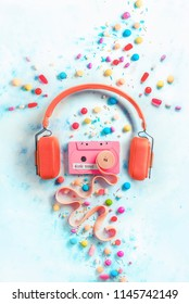 Headphones with a pink cassette tape with a tape of bubble gum in a gentle and sweet music concept with copy space. Candies, sprinkles, and marmalades in a pastel color flat lay with sweets
