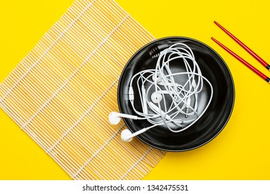 Headphones in a plate on a bamboo mat and a bright yellow background, next are chopsticks. Concept of musical taste. Close-up.