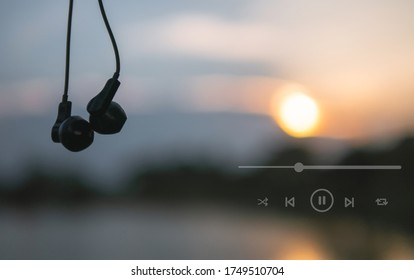 Headphones and playlist listen to music at sunset
