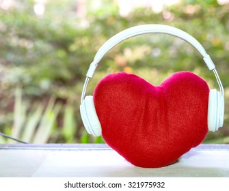Headphones with red heart on table. music of love. valentine's day concept