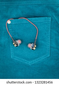 Headphones with red wire sticking out of the pocket of green jeans.
