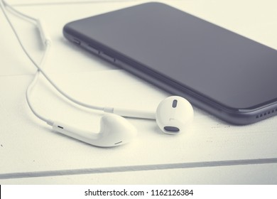 Headphones with the smartphone lie on wooden white boards. Photograph filtered in a hipster style with a shallow depth of field.