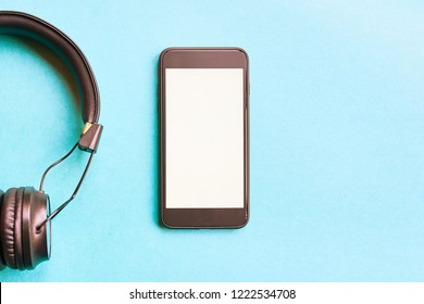Headphones and smartphone on colorful background. Flat lay concept: headphones and telephone on blue pastel backgrounds.