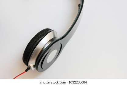 Headphones Stereo Gadget for Music Listening Isolated on White Table Background. Modern Electronic Device with Red Cord, Portable Black Headphones with Empty Copy Space. Technology Music Concept Image