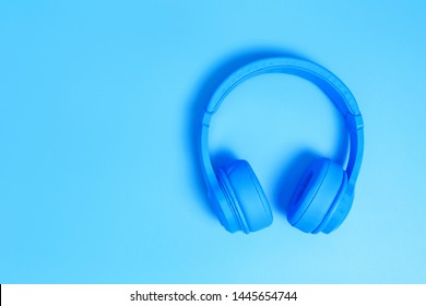 a headphones, Top view of headphones on blue background. Minimalist photo of earphones with copy space. blue dj headphones, Top view blue headphones on blue background