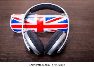 Headphones with UK flag pencil case concept on wooden background