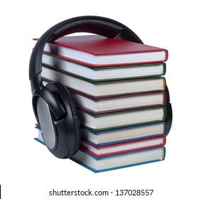 Headphones worn on a stack of books with color covers isolated on white background.