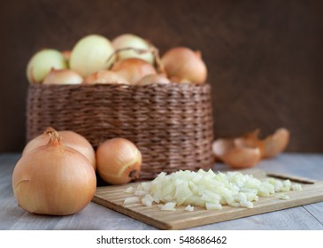 A lot of heads bulb onion in a wicker basket. Large onions in a large wicker bowl. Sliced onions on a cutting board to prepare meals. Bulb onion is good for health.