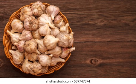 heads of garlic in a wicker basket on a wooden background