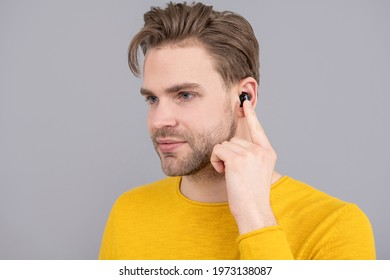 headset device accessory. new technology. Man point finger at wireless earbud earphones inside ear. Listening with headphones. make music a pleasant experience.