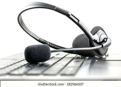 Headset lying on a laptop computer keyboard conceptual of telemarketing, call center, client services or online support.