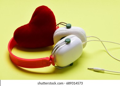 Headset for music with love symbol. Headphones in white and red color and soft toy heart. Modern and stylish earphones on light yellow background. Love, leisure and music concept