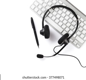 Headset, pen and keyboard. Call center support. Isolated on white background