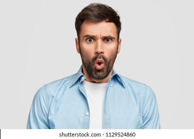Headshot of amazed astonished bearded guy looks in displeasure, frowns face angrily, feels scared of some difficulties in life, dressed in blue shirt, stands against white wall. Negative emotions