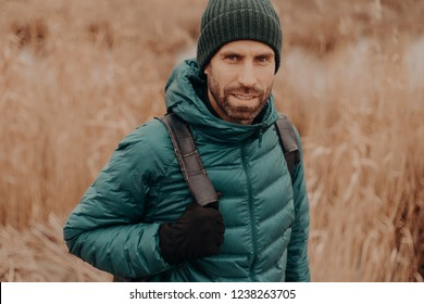 Headshot of atrractive blue eyed man has dark stubble, wears hat, jacket, gloves, carries rucksack, has outdoor stroll, models against blurred background. People, leisure, traveling and rest concept