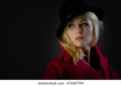 Headshot of an attractive blonde woman with a black fedora
