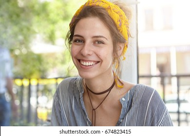 Headshot of attractive female with dark eyes, pure skin and pleasant smile wearing yellow scarf on head and shirt sitting outdoors at terrace relaxing during her weekends. People and beauty concept