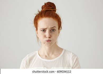 Headshot of attractive funny young female with ginger hair dressed in white blouse feeling displeased or uncomfortable with something, blowing cheeks and frowning. Human face expressions and emotions