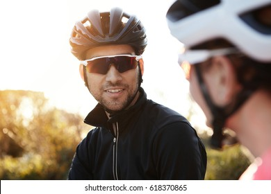 Headshot of attractive and handsome European cyclist with stubble wearing in helmet and sporty sunglasses, smiling while talking to his female friend, sun shining in background.Selective focus