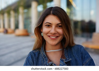Headshot of attractive latin woman with pretty face looking and smiling cheerfully at camera, posing in urban surroundings on summer day, wearing trendy accessories and denim jacket. City lifestyle