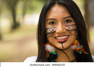 Headshot beautiful Amazonian woman, indigenous facial paint and earrings with colorful feathers, posing happily for camera in park environment, forest background