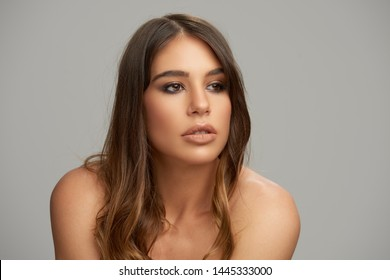 Headshot of beautiful Caucasian brunette posing in front of grey background. Beauty photography.