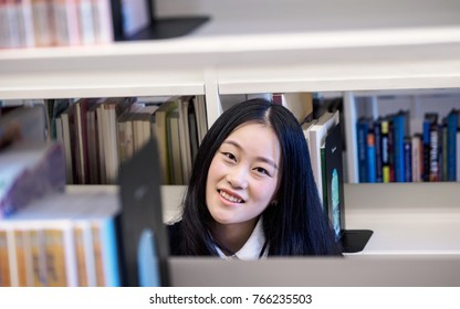 Headshot of a beautiful Chinese student smiling behind the bookshelf in college library, library and education concept.