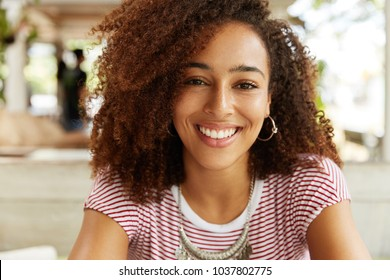 Headshot of beautiful dark skinned female with happy expression has Afro hairstyle, demonstrates perfect white even teeth, has pleased smile. Stylish young African American woman rests indoor