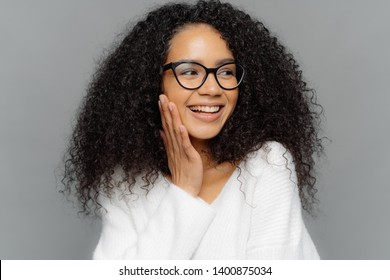 Headshot of beautiful dark skinned female model touches cheek gently, has charming smile on face, looks happily away, has curly Afro hair, wears spectacles and white jumper, isolated on grey wall
