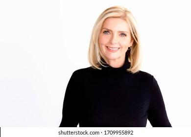 Headshot von schöner älterer Frau, die sich die Kamera ansieht und lächelt, während sie auf isoliertem weißem Hintergrund steht.