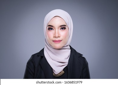 A headshot of a beautiful Muslim woman in hijab and officewear on grey background.
