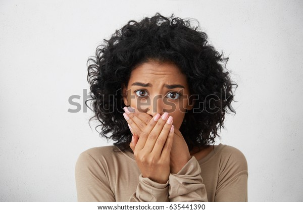 Headshot of beautiful scared young dark-skinned European female with curly hairstyle closing mouth not to scream, feeling frightened and terrified, her eyes and look full of fear and terror